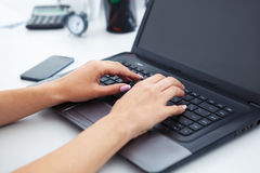 Plan rapproché des mains de femme fonctionnant avec l'ordinateur portable Photos stock
