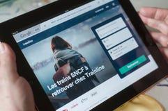 Plan rapproché des mains de femme sur la page d'accueil du site Web de réservation de SNCF sur le comprimé Photographie stock libre de droits