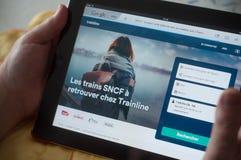 Plan rapproché des mains de femme sur la page d'accueil du site Web de réservation de SNCF sur le comprimé Image libre de droits