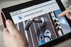 Plan rapproché des mains de femme sur la page d'accueil du site Web de serrurier sur le comprimé Photographie stock
