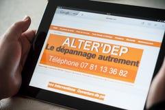 Plan rapproché des mains de femme sur la page d'accueil du site Web de serrurier sur le comprimé Photographie stock libre de droits