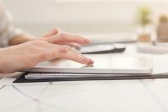 Plan rapproché des mains de femme utilisant le comprimé et du compte sur la calculatrice Photo stock