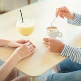 Plan rapproché des mains de femmes sur la table tout en buvant le café et le smoothie Photographie stock libre de droits