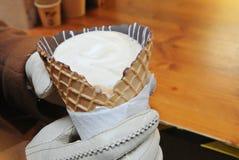 Plan rapproché des mains de fille de femme dans les gants blancs tenant un cornettocc Image libre de droits
