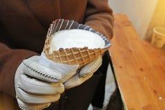 Plan rapproché des mains de fille de femme dans les gants blancs tenant un cornettocc Photographie stock