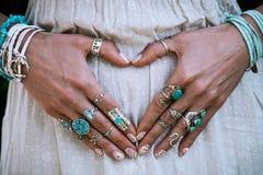 Plan rapproché des mains de jeune femme dans la forme de coeur avec le sort de l'étable de boho Image stock
