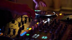 Plan rapproché des mains de jockey de disque travaillant au mélangeur dans les lumières colorées de la boîte de nuit banque de vidéos