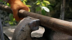 Plan rapproché des mains de l'homme dans les gants fonctionnants maintenus dans un tuyau rouillé vice en métal banque de vidéos
