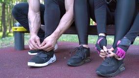 Plan rapproché des mains de l'homme et de la femme attachant des dentelles sur des espadrilles avant de former dehors banque de vidéos