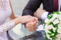 Plan rapproché des mains de mariage avec des anneaux Photo stock