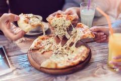 Plan rapproché des mains de personnes prenant des tranches de pizza Image stock