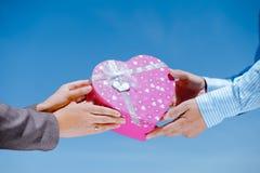 Plan rapproché des mains du couple heureux avec le coeur rose Images stock