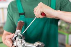 Plan rapproché des mains du mécanicien de bicyclette au travail Images stock