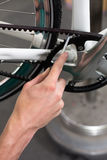 Plan rapproché des mains du mécanicien de bicyclette au travail Image libre de droits