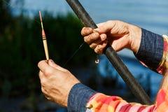 Plan rapproché des mains du pêcheur Pêcheur tenant un poteau de pêche, un bobber et un crochet Image stock