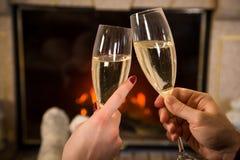 Plan rapproché des mains du ` s de couples avec le verre de champagne près de cheminée Photos stock