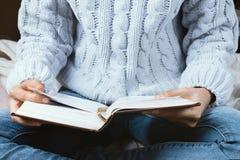 Plan rapproché des mains du ` s de femme dans le chandail tenant le livre Image stock