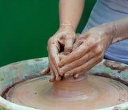 Plan rapproché des mains effectuant la poterie sur une roue Image libre de droits
