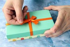 Plan rapproché des mains femelles déballant un présent image stock