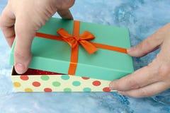 Plan rapproché des mains femelles déballant un présent photos stock