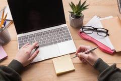 Plan rapproché des mains femelles dactylographiant sur l'ordinateur portable et écrivant des notes Images stock