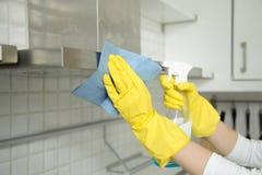 Plan rapproché des mains femelles dans les gants nettoyant le capot d'extracteur Image libre de droits