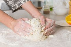 Plan rapproché des mains femelles malaxant la pâte dans la cuisine minimalistic moderne Image stock