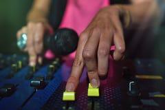 Plan rapproché des mains femelles sur une console de disc-jockey avec le microphone image stock