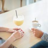 Plan rapproché des mains femelles tout en buvant le café et le smoothie Image stock