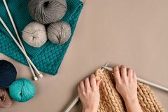 Plan rapproché des mains femelles tricotant la couleur de beige de chandail ou de plaid de laine Vue supérieure Photos stock