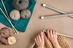 Plan rapproché des mains femelles tricotant la couleur de beige de chandail ou de plaid de laine Vue supérieure Photographie stock