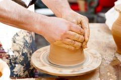Plan rapproché des mains fonctionnant avec de l'argile sur l'artisan de plaque tournante image libre de droits