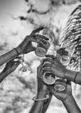 Plan rapproché des mains grillant avec des verres de bière Photos stock