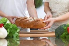 Plan rapproché des mains humaines coupant en tranches le pain dans une cuisine Amis ayant l'amusement tout en préparant la salade Photographie stock