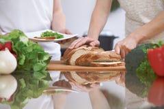 Plan rapproché des mains humaines coupant en tranches le pain dans une cuisine Amis ayant l'amusement tout en préparant la salade Photographie stock libre de droits