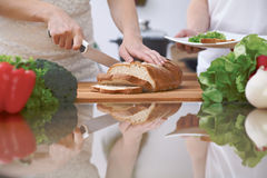 Plan rapproché des mains humaines coupant en tranches le pain dans une cuisine Amis ayant l'amusement tout en préparant la salade Images stock