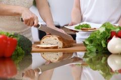 Plan rapproché des mains humaines coupant en tranches le pain dans une cuisine Amis ayant l'amusement tout en préparant la salade Image stock