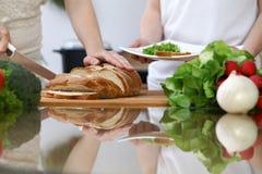 Plan rapproché des mains humaines coupant en tranches le pain dans une cuisine Amis ayant l'amusement tout en faisant cuire dans  Images libres de droits