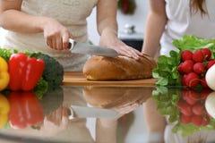 Plan rapproché des mains humaines coupant en tranches le pain dans une cuisine Amis ayant l'amusement tout en faisant cuire dans  Photo stock