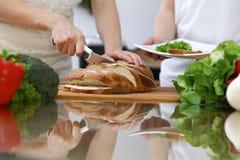 Plan rapproché des mains humaines coupant en tranches le pain dans une cuisine Amis ayant l'amusement tout en faisant cuire dans  Photos libres de droits