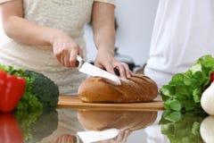 Plan rapproché des mains humaines coupant en tranches le pain dans une cuisine Amis ayant l'amusement tout en faisant cuire dans  Photographie stock
