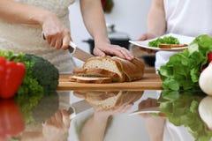Plan rapproché des mains humaines coupant en tranches le pain dans une cuisine Amis ayant l'amusement tout en faisant cuire dans  Photographie stock libre de droits