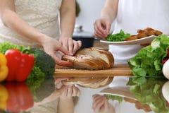 Plan rapproché des mains humaines coupant en tranches le pain dans une cuisine Amis ayant l'amusement tout en faisant cuire dans  Photos stock