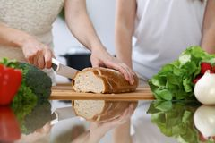 Plan rapproché des mains humaines coupant en tranches le pain dans une cuisine Amis ayant l'amusement tout en faisant cuire dans  Image stock