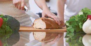 Plan rapproché des mains humaines coupant en tranches le pain dans une cuisine Amis ayant l'amusement tout en préparant la salade Photo libre de droits