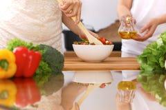 Plan rapproché des mains humaines faisant cuire dans la cuisine Mère et fille ou deux amis féminins coupant des légumes pour la s Images libres de droits
