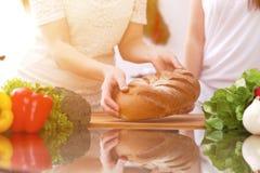 Plan rapproché des mains humaines faisant cuire dans la cuisine Mère et fille ou deux amis féminins coupant le pain Repas sain Photos libres de droits
