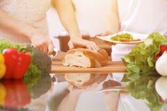 Plan rapproché des mains humaines faisant cuire dans la cuisine Mère et fille ou deux amis féminins coupant le pain Repas sain Image stock
