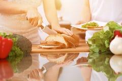 Plan rapproché des mains humaines faisant cuire dans la cuisine Mère et fille ou deux amis féminins coupant le pain Repas sain Images stock