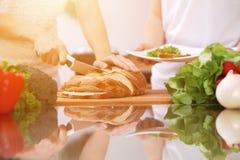 Plan rapproché des mains humaines faisant cuire dans la cuisine Mère et fille ou deux amis féminins coupant le pain Repas sain Photo libre de droits